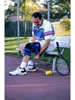 Picture of a man wearing a knee-brace, playing tennis