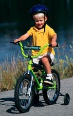 Picture of young boy, with a helmet, riding a bicycle