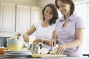 Mother and daughter cooking together in a kitchen
