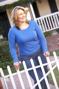 Woman standing by a fence in the front yard