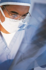 Doctor wearing a surgical mask looking at a chest X-ray