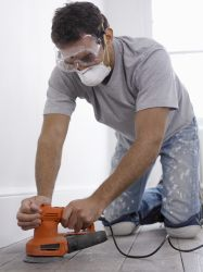 Man wearing a face mask while sanding a wood floor.