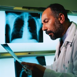 Photograph of a radiologist reading an X-ray