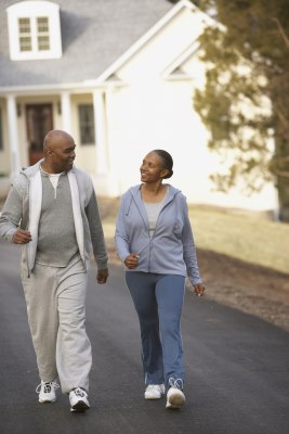 A middle-aged couple walking down the street in a residential neighborhood